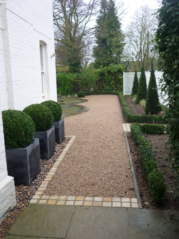 Faux lead planters box hedge taxus pyramids and timber trellis