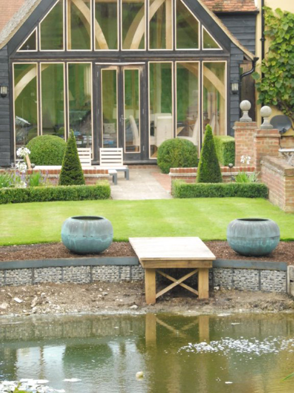 Pond, jetty, gabion retaining wall and topiary planting